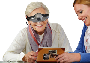 Woman using low vision glasses to see photos