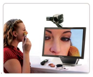 Woman using desktop magnifier to apply makeup
